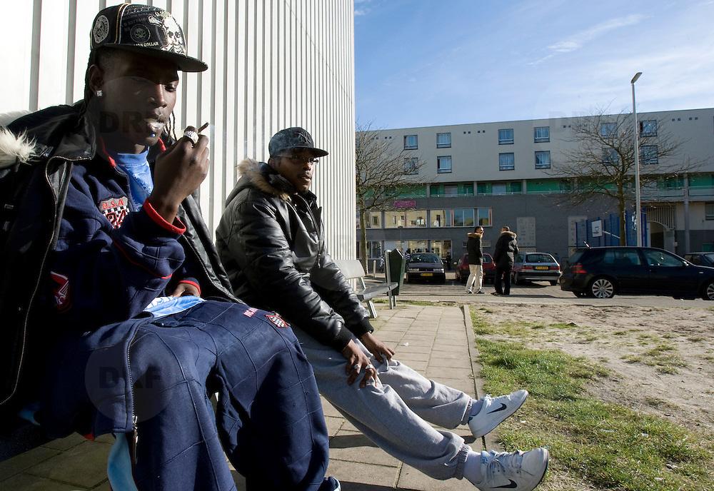 Nederland Rotterdam 14 maart 2008 20080314 .Allochtone jongeren zitten op bankje in zonnetje en roken een blowtje in achterstandswijk Hillesluis Rotterdam Zuid..Foto David Rozing
