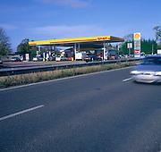Car blurred speeding past Shell petrol station Britain