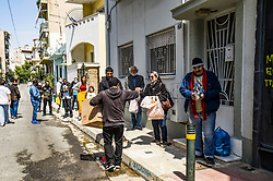 Konstantinos Polychronopoulos (L) distributes meals to migrants, outside the premises of the social kitchen 'The other human' in Athens, Greece, on 15 April 2020. - The social kitchen appeared in the middle of the Greek financial crisis, adapting now during the COVID-19 pandemic and confinement, distributing meals to unemployed, migrants, homeless and elderly people.<br />