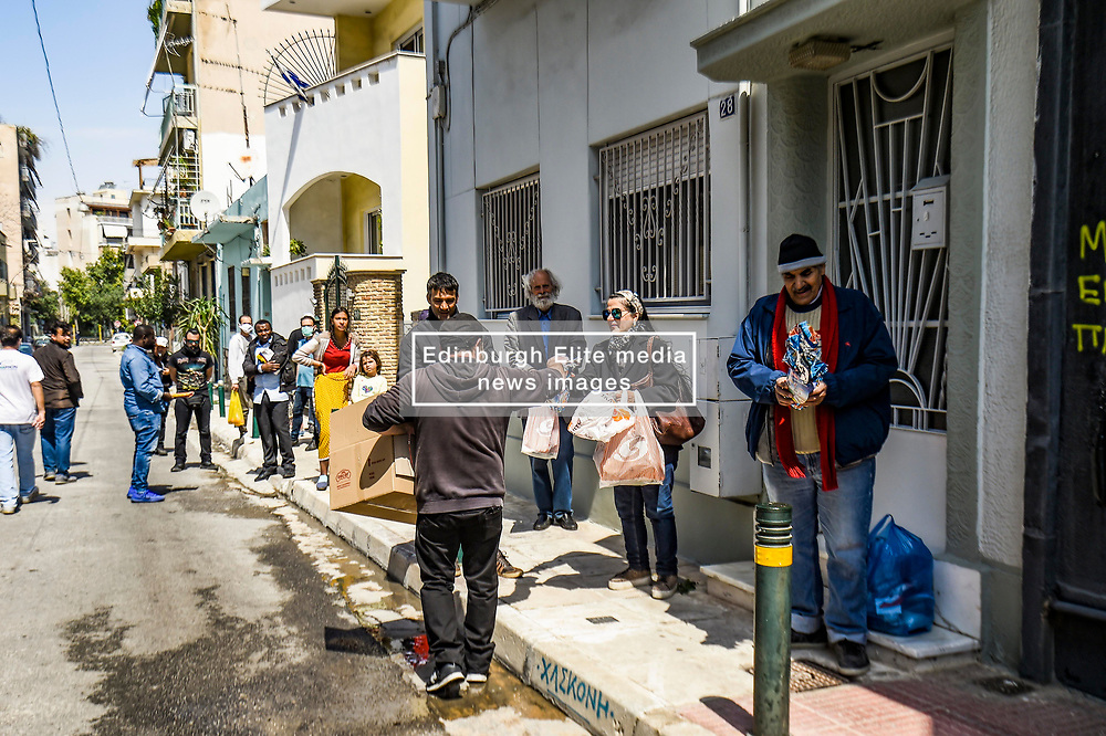 Konstantinos Polychronopoulos (L) distributes meals to migrants, outside the premises of the social kitchen 'The other human' in Athens, Greece, on 15 April 2020. - The social kitchen appeared in the middle of the Greek financial crisis, adapting now during the COVID-19 pandemic and confinement, distributing meals to unemployed, migrants, homeless and elderly people.<br /> <br /> <br /> Dimitris Lampropoulos    15 April 2020