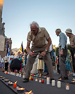 Riga, Latvia - August 23, 2015: A man sets a candle on the ground in Latvia's capital, Riga, to commemorate the 26th anniversary of the Baltic Way. On August 23, 1989, approximately two million people held hands in a peaceful protest, forming a human chain spanning some 400 miles across Estonia, Latvia, and Lithuania. The Baltic Way itself was held on the 50th anniversary of the Molotov–Ribbentrop Pact, in which Hitler and Stalin secretly agreed that the three Baltic countries would be occupied by the Soviet Union.<br /> <br /> On September 6, 1991, the Soviet Union recognized the independence of three Baltic states.