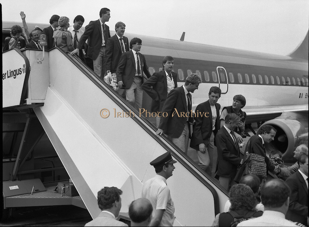 Irish Soccer Team Welcomed Home.   (R81)..1988..19.06.1988..06.19.1988..19th June 1988..After their great success in Germany in Euro 88, the Irish soccer team had a triumphant homecoming. An Taoiseach, Charles Haughey TD and his government were to the forefront of the welcome. Thousands of fans thronged the airport and all the approach roads in the hope of seeing the team. The full squad is as follows..1.GK.Packie Bonner. Celtic.2.DF.Chris Morris. Celtic.3.DF.Chris Hughton  Tottenham Hotspur.4.DF.Mick McCarthy. Celtic.5.DF.Kevin Moran. Manchester United.6.MF.Ronnie Whelan. Liverpool.7.MF.Paul McGrath. Manchester United.8.MF.Ray Houghton. Liverpool.9.FW.John Aldridge. Liverpool.10.FW.Frank Stapleton Derby County.11.MF.Tony Galvin. Sheffield Wednesday.12.FW.Tony Cascarino. Millwall.13.MF.Liam O'Brien. Manchester United.14.FW.David Kelly. Walsall.15.MF.Kevin Sheedy. Everton.16.GK.Gerry Peyton. Bournemouth.17.FW.John Byrne. Le Havre.18.FW.John Sheridan. Leeds United.19.DF.John Anderson. Newcastle United.20.FW.Niall Quinn. Arsenal..Image shows the Irish team descending from the Aer Lingus aircraft on their arrival at Dublin Airport.