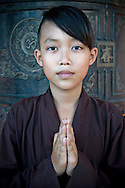 A young vietnamese monk joins hands in prayer and looks straight at the camera. Khanh Hoa area, Vietnam, Asia
