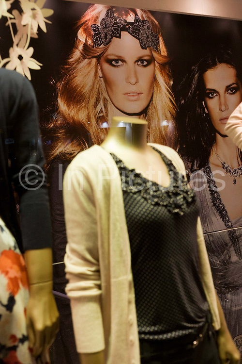 A model's face appears to belong to a womens' fashion window mannequin in Chelsea. Juxtaposed with the woman's head over the neck and shoulders of the mannequin, we get the sense of a whole body, as if caught as one person at a party or social event. This shop is on Chelsea's Kings Road, one of the trendiest streets on which buy pricey clothes and accessories.