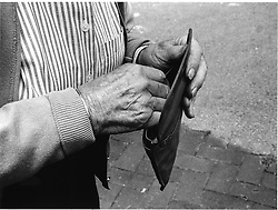 Closeup of elderly woman counting money in purse,