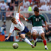 Mexico's Jesus Arellano tackles USA's Eddie Lewis
