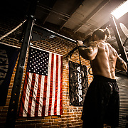 Athlete doing pull-ups in a CrossFit gym in Reno, NV.