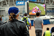 A policewoman watching the 2008 Rugby League Grand Final on a big screen set up outside Olympic Stadium. Sydney, Australia