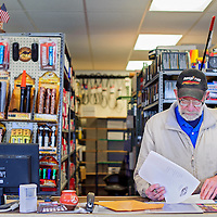 032814       Cable Hoover<br /> <br /> Poor Boys Auto Supply owner Rob Miller checks paperwork at the counter at his new location on Aztec Avenue Friday.
