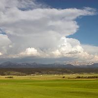 Summer thunderheads tower over Idaho farmlands under western slopes of the Teton Mountains, between Drummond and Tetonia.