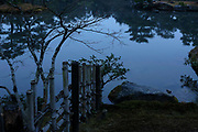 Dusk settling over a lake with bamboo fence running to water's edge. Kyoto, japan.