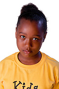 An individual child wearing a yellow t-shirt, with a sad, lonely, hurt, afraid, worried  or depressed expression.
