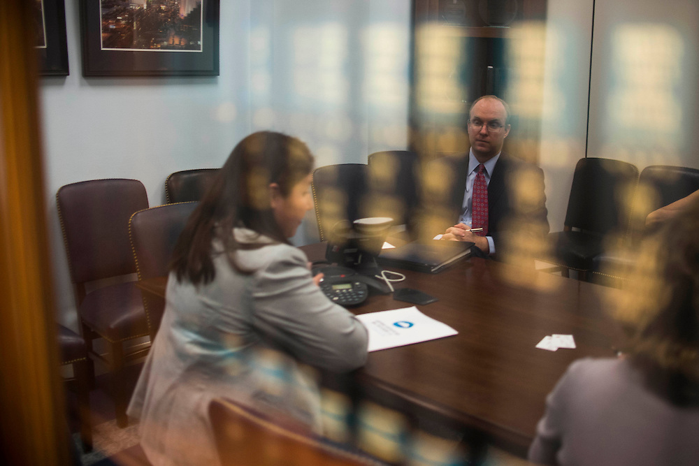 Photo by Matt Roth...Reflected in a bookshelf window, Sarah Saylor, Climate Lobbyist, for Earthjustice, left, talks to aides who work for Nevada Senator Harry Reid in a meeting room inside the Hart Senate Office Building in Washington, D.C. on Wednesday, May 15, 2013. They have a meeting with a few of Senator Reid's aides to discuss clean air as part of the Fifty States United for Healthy Air campaign.