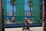 Reflections of the beach area with cyclists reflected in the modern complexes windows, Barcelonetta, the port area of, Barcelona, Spain.