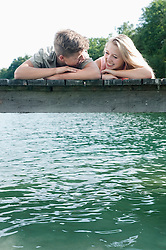 Teenage couple lying side by side on a jetty at lake