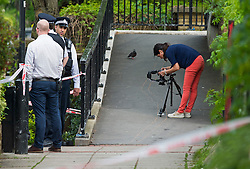 © London News Pictures. 11/05/2015. Evidence being photographed, which looks like drag marks, over a footpath crossing the canal at Little Venice in West London where a body has been found in a suitcase. The discovery was made on the Grand Union Canal near Delamere Terrace. Photo credit: Ben Cawthra/LNP