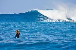 Woman surfer, waiting for a rare big ocean wave in Kona Coast, Keauhou Bay, Big Island, Hawaii, Pacific Ocean.