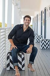 good looking man sitting on a motel deck