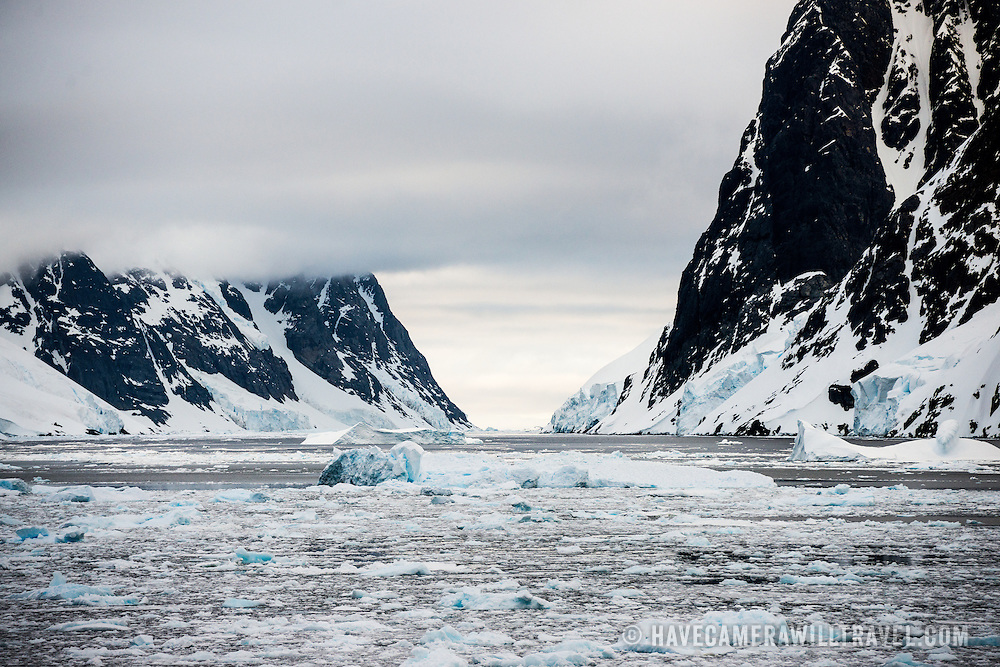"""Sheets of sea ice and brash ice fkoat on the water of the Lemaire Channel, with steep mountain cliffs rising out of the water on either side. The Lemaire Channel is sometimes referred to as """"Kodak Gap"""" in a nod to its famously scenic views."""