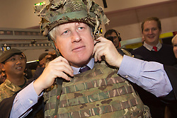 """© Licensed to London News Pictures. 22/11/2013. London, England. Pictured: Boris Johnson dresses up as a soldier in a bullet-proof vest and a helmet. Boris Johnson, Mayor of London, today visited the UK's biggest jobs and careers fair """"Skills London"""" at the Excel Exhibition Centre and went on a walkabout where he visited stands and performed some of the jobs on show. Photo credit: Bettina Strenske/LNP"""
