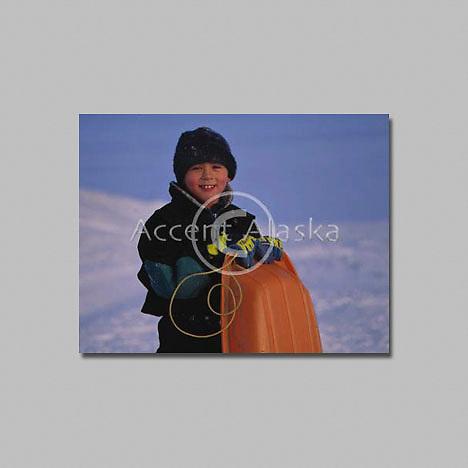 Alaska. Nome. Young eskimo boy sleds on sea ice in the Bering Sea.