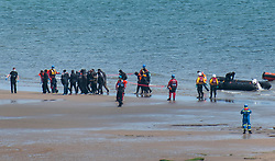 © Licensed to London News Pictures. 16/05/2020. Hastings, UK. Migrants are helped ashore at Pett Level near Hastings in East Sussex by the emergency services after crossing the English Channel earlier today in an inflatable boat (R). The group, possibly numbering up to 20 people including young children, were taken under tow by the Hastings Lifeboat and brought ashore by the Pett Level Independent Rescue Boat. They were met by coastguard and other government officials. Photo credit: Andrew Heather/LNP