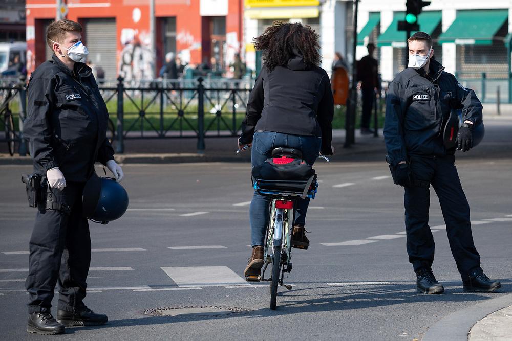 An die 200 Demonstranten mit Atemschutzmasken protestieren während der Verordnung mit Ausgansbeschränkungen und Kontaktverbot zur Eindämmung der COVID-19 - Pandemie (Coronavirus SARS-CoV-2)  unangemeldet und mit Sicherheitsabstand am Kottbusser Tor in Berlin Kreuzberg gegen Zwangsräumungen, soziale Missstände und für eine Aufnahe von Geflüchteten. Polizisten mit Atemschutzmasken sichern die Straße.<br /> <br /> [© Christian Mang - Veroeffentlichung nur gg. Honorar (zzgl. MwSt.), Urhebervermerk und Beleg. Nur für redaktionelle Nutzung - Publication only with licence fee payment, copyright notice and voucher copy. For editorial use only - No model release. No property release. Kontakt: mail@christianmang.com.]