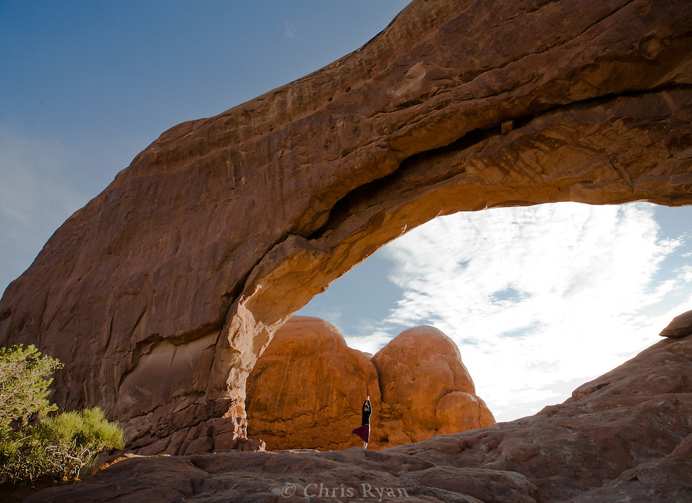 Yoga pose beneath North Window arch at Arches National Park, Utah