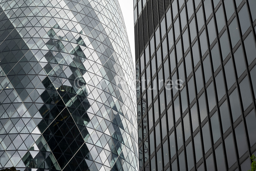 Views of reflections looking towards 1 St Mary Axe aka the Gherkin on 26th May 2021 in London, United Kingdom. As the financial district grows in height, the architecture has changed the face of London with many different companies occupying the various floors and levels, some of which remain empty as overseas investments.