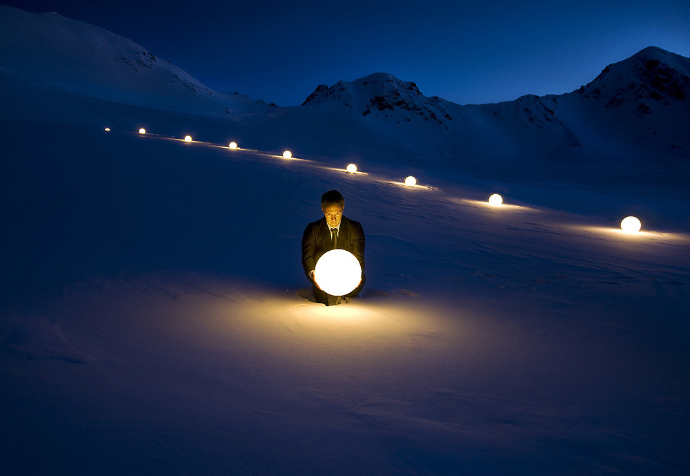 Business man holding a light ball in his hands surrounded by snow on a glacier at night
