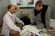 A mentally ill man is examined by Mohammed Omar Faridi, a pir at the Shareef Dargah in New Delhi. Delhi is typical of many Indian cities in that it has very few trained psychiatrists and many people still consult holy men for traditional solutions to their psychiatric needs. As India progresses materially and embraces the market and as traditional familiar and social ties are increasingly broken, incidences of mental health issues appear to be rising.