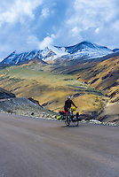Traveler bicycling over 17,582 foot Tanglangla Pass (the second highest pass in the world), in the Himalayas along the Leh-Manali Highway, Ladakh; Jammu and Kashmir state, India.