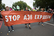 Environmental activists hold a Stop A38 Expansion banner on the Extinction Rebellion Stop The Harm march during the fourth day of Impossible Rebellion protests on 26th August 2021 in London, United Kingdom. Extinction Rebellion are calling on the UK government to cease all new fossil fuel investment with immediate effect.