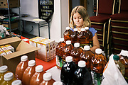 """16 SEPTEMBER 2020 - MITCHELLVILLE, IOWA: A volunteer puts out fruit juice in the pantry at the Heritage Word of Life Church. There is no grocery store in Mitchellville, a small community in eastern Polk County. It doesn't qualify as a """"food desert"""" under USDA guidelines because there are grocery stores within 10 miles in neighboring communities, but based on state data, Mitchellville is the poorest community in Polk County (which includes the Des Moines metropolitan area). The Mitchellville zip code has the lowest per capita income in Polk County. Many people don't own cars and can't get to neighboring communities to buy groceries. Every day someone from the Mitchellville library picks up hot meals from a nearby town and distributes them in the library. Heritage Word of Life, a church across the street from Library, has a food pantry in their Fellowship Room where people can pick up fresh vegetables, staples, and hygiene needs.       PHOTO BY JACK KURTZ"""