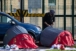 Sandwich, UK. 4th October, 2021. A Kent Police officer monitors two Palestine Action activists in small tents locked onto a car to block an entrance to the Instro Precision factory in Discovery Park. Instro Precision is a subsidiary of Elbit Systems, Israel's largest publicly-traded arms company which markets drones used extensively by the Israeli military in Gaza as 'battle-proven', and it supplies 'high precision military equipment'. Palestine Action contends that equipment sold by Instro Precision has been used by the Israeli military against the civilian population of Gaza.