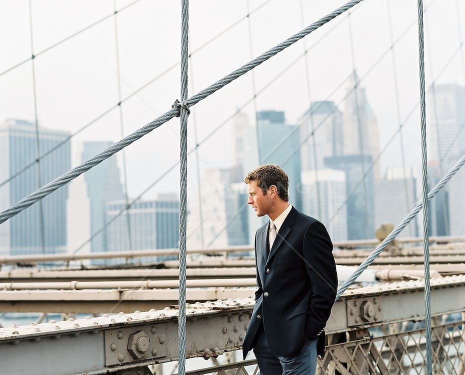 Businessman looking at the city from The Brooklyn Bridge