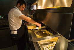 Chef Eddie Macit places battered 'prawns' made from Japanese potatoes in the fryer at London's first totally vegan chippy in Hackney, North East London. Hackney, London, October 08 2018.