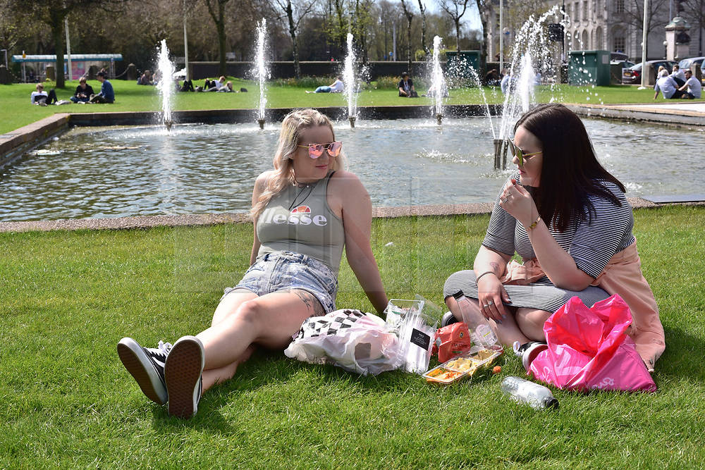 ©Licenced to London News Pictures. 18/04/18. Cardiff, Wales,UK. The hottest day of the year so far draws office workers and students out to picnic and sunbathe in Cardiff outside City Hall. Temperatures of 20°C and a rare glimpse of the sun make all the difference in what has been a very cold and wet start to 2018. .Photo credit IAN HOMER/LNP