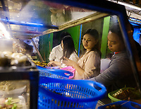 YANGON, MYANMAR - CIRCA DECEMBER 2017: Portrait of Burmese people ordering street food Yangon at night.