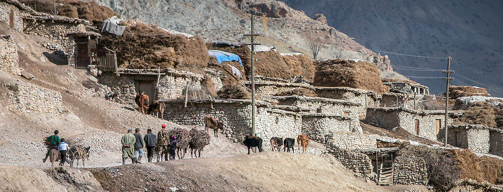 Stock landscape photograph of Anzob village in autumn livery on the Dushanbe Road in Tajikistan. Each of the stone walled houses have piles of hay on its roof for insulation and winter feed for livestock.