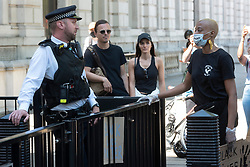© Licensed to London News Pictures. 31/05/2020. London, UK. Supporters for the group Black Lives Matter demonstrate against police officers outside Downing St for the American George Floyd who died whilst being arrested by US policemen Derek Chauvin. Photo credit: London News Pictures.