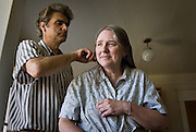 ALZHEIMERS STORY; BETSY, JEFF AND EMILY MEYER AT HOME BEFORE BETSY IS MOVED TO ADULT CARE HOME 071107<br /> <br /> Standing up for long periods of time became one of Betsy's routines at home;  Jeff brushes Betsy's hair, part of her daily personal care that he took upon himself.