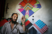 Noor Agha, 52, says no one can win his kite making next to a kite ordered by an American client (with both Afghan and American flags) in the house, Kabul, Afghanistan, Monday, July, 9, 2007. Noor Agha is a renowned kite maker who made kites for the movie makers of the best-selling novel, The Kite Runner, which will be distributed by Dreamworks and Paramount Vantage in Nov. this year. Noor Agha's wives, using their special glue, help him produce enough kites to please the clients' needs.