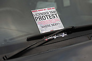 Licensed taxi drivers block the traffic in Parliament Square between 1pm-4pm in protest against traffic policies, 11th of February 2019, Central London, United Kingdom.  A flyer in the window of a cab explaining the protest. The disgruntled taxi drivers feel squeezed by local government transport policies. TThey say they will continue their protest and blockade the square every other day the same time until they feel the Mayor of London listens to them.