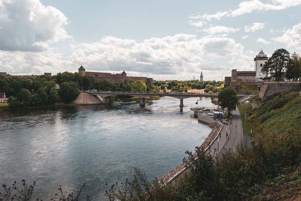 Narva, Estonia - July 24, 2015: The Narva River separates the cities of Narva, Estonia (right) and Ivangorod, Russia (right). The tower on the right is part of Herman Castle, first built by the Danes in the 13th century. The castle in Russia, on the left, was built by Ivan III of Muscovy in 1492.