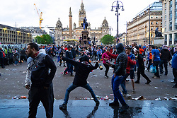 Glasgow, Scotland, UK. 15 May 202. Rangers football supporters  celebrating 55th league victory are cleared from George Square by police in riot gear on Saturday evening. In very violent scenes police were pelted with bottles and items from a nearby construction site as police pushed the supporters into the south west corner of the square. Pic; Man throws bottle towards police line.  Iain Masterton/Alamy Live News.