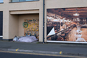 Homeless persons personal effects and bedding in a disused doorway of a building and next to a large scale poster of a restaurant dining room in the city centre on 30th March 2021 in Birmingham, United Kingdom. The image of both affluence and wealth contrasts greatly with the subject of homelessness and poverty.
