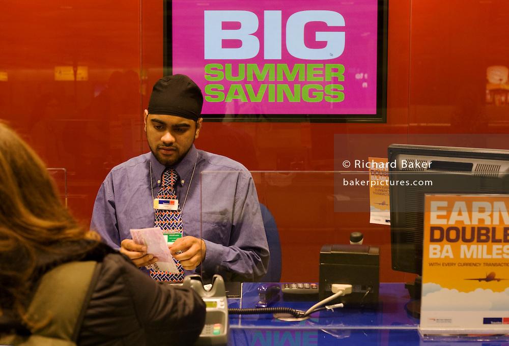Travelex bureau de change assistant serves currency to passenger at Heathrow airport's terminal 5