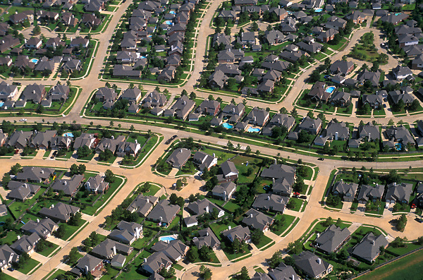 Aerial view of winding streets and cul de sacs in a suburban Houston neighborhood.