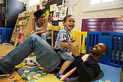 A young father bonding with his baby son in the children's play area during a family visit in HMP Brixton, South London on the 26th of July 2016, London United Kingdom. The Prisoner Advice & Care Trust (PACT) organise special family days that help the men inside the prison connect with and support their partners and children on the outside. (photo by Andy Aitchison)